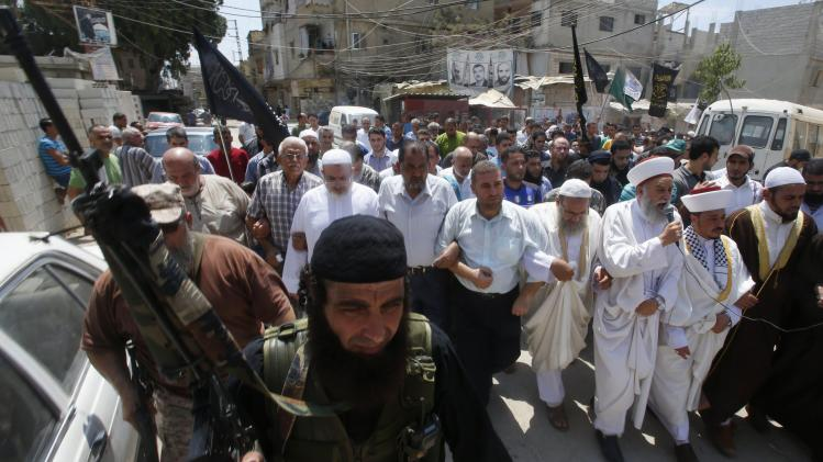 Palestinian gunmen escort a demonstration held to show solidarity with the Palestinians in Gaza, after Friday prayers in the Ain al-Hilweh Palestinian refugee camp near the port-city of Sidon