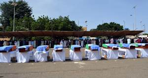 The coffins of nine United Nations soldiers are draped …