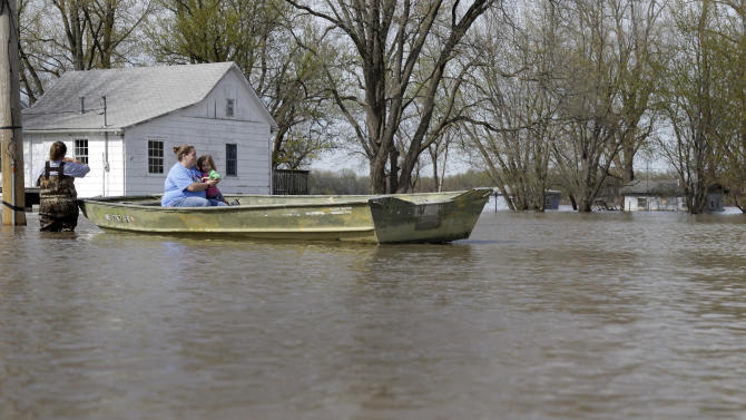Barbara Adams holds family friend Haley Wright, 4, at right, while being pulled along in a boat by Adams' mother, Julia Dowell, left, Monday, April 22, 2013, in Clarksville, Mo. The swollen Mississippi River has strained a hastily erected makeshift floodwall in Clarksville, creating two trouble spots that volunteers were scrambling to patch. (AP Photo/Jeff Roberson)