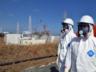 Japanese workers stand near the stricken Fukushima nuclear plant in Okuma. The operator of the crippled Fukushima nuclear plant admitted it had played down the risks of a tsunami to the facility for fear of the financial and regulatory costs