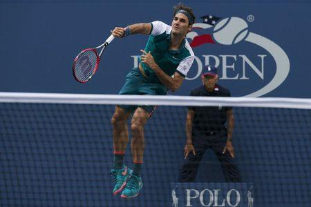 Federer of Switzerland serves the ball to Mayer of Argentina in their first round match at the U.S. Open Championships tennis tournament in New York