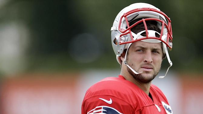 In this Aug. 7, 2013, file photo, New England Patriots' Tim Tebow walks onto the field during a joint workout with the Philadelphia Eagles at NFL football training camp in Philadelphia. Tebow says he is not done with the NFL even though helping ESPN launch the SEC Network was too good an opportunity to pass up. Tebow stresses he will keep training in hopes of returning to the NFL as a quarterback