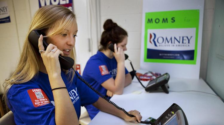 Shannon Westfield, 20, left, and Jane Kernan, 16, make calls for the Romney campaign while wearing quick response code stickers, known as QR codes, in Fairfax, Va., on Tuesday, June 19, 2012.   The presidential ground game has gone high tech, marrying old-school organizing work with innovative digital tools.   The T-shirts that Romney campaign volunteers wear in Virginia feature a digital code that voters can zap with their smart phones to learn more about the Republican presidential hopeful, which gives Romney field organizers valuable information on how to reach them in the future.  (AP Photo/Jacquelyn Martin)