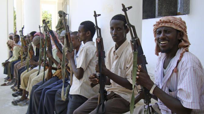In this photo taken Tuesday, Oct. 13, 2009, armed men from the al-Shabab militant group are paraded at the presidential palace in Mogadishu, Somalia after defecting from the al-Qaida linked group to join government forces. Security services in Mogadishu have seen a new wave of defections from the Islamic extremists of al-Shabab, men who can provide valuable information or scouting services for the police, military and intelligence service. (AP Photo/Farah Abdi Warsameh)