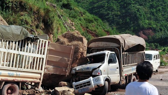 A man looks at the trucks damaged by fallen rocks after an  earthquake in Zhaotong town, Yiliang County, southwest China's Yunnan Province, Friday, Sept. 7, 2012. A series of earthquakes collapsed houses and triggered landslides Friday in a remote mountainous part of southwestern China where damage was preventing rescues and communications were disrupted. At least 64 deaths have been reported. (AP Photo) CHINA OUT