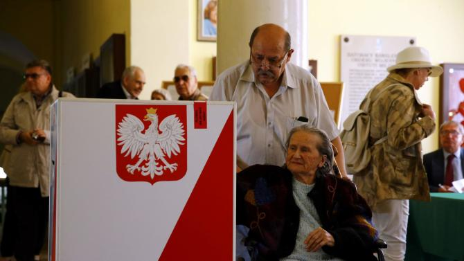 A man helps a woman in a wheelchair to cast her ballot at a polling station in Warsaw