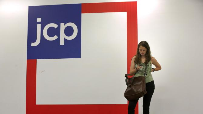 Woman checks her phone outside the entrance of a J.C. Penney store in New York in this file photo
