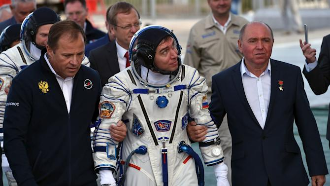 Russian cosmonaut Sergei Volkov, his father Soviet cosmonaut Aleksander Volkov and Roskosmos agency's head Igor Komarov go to board the Soyuz TMA-18M spacecraft at the Russian-leased Baikonur cosmodrome