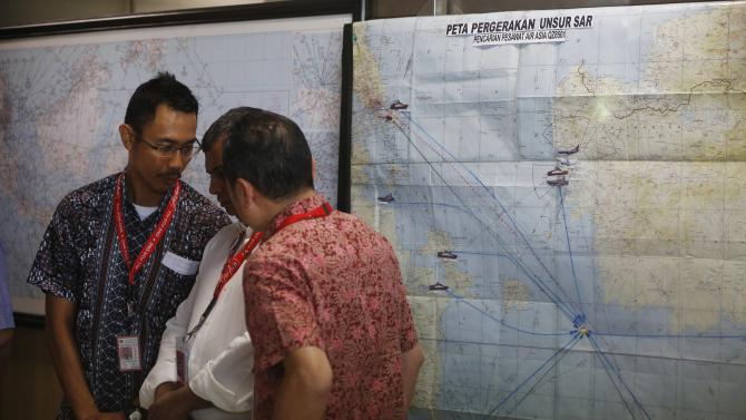 Indonesia Air Asia CEO Widyatmoko talks with Air Asia CEO Fernandes in front of map for the joint Search and Rescue team for AirAsia flight QZ8501, at Surabaya's Juanda International Airport