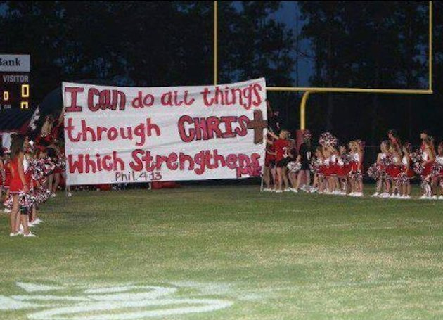 Kountze cheerleaders hold up one of their biblically-related signs — Facebook