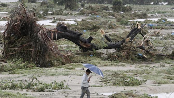 A walks past an uprooted tree that lies on the river bed of the swollen Shonai River at Kasugai, central Japan,on Wednesday Sept. 21, 2011 as powerful Typhoon Roke lashes across central Japan with heavy rains and sustained winds of up to 100 mph (162 kph). (AP Photo/Kyodo News) JAPAN OUT, MANDATORY CREDIT, NO LICENSING IN CHINA, FRANCE, HONG KONG, JAPAN AND SOUTH KOREA