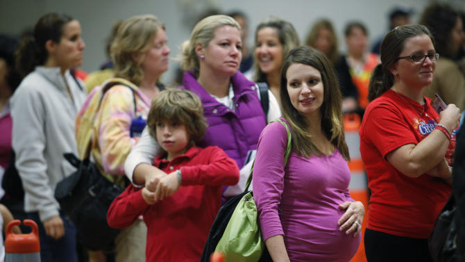 FILE - In this Thursday, Oct. 29, 2009 file photo, Nicole Andreacchio, second right, who is seven months pregnant waits in line to receive the swine flu vaccine from the Montgomery County Health Department at Congregation Beth Or in Maple Glen, Pa. A large study released by the New England Journal of Medicine on Wednesday, Jan. 16, 2013 offers reassuring news for pregnant women worried about getting a flu shot. The research found no evidence that the vaccine increases the risk of losing a fetus, and may prevent some fetal deaths. (AP Photo/Matt Rourke)