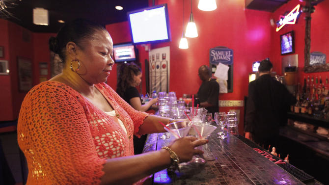 In this June 8, 2012 photo, Mary Lindsey, owner if the Jokes and Notes comedy club buses drinks for her waitresses during the first of two shows in Chicago's Bronzeville neighborhood. African-American female club owners are a rarity in the industry of comedy, but Lindsey is breaking barriers and uplifting a community by providing a place where raw comedic talent can hone their skills. (AP Photo/Charles Rex Arbogast)