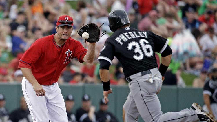 Chicago White Sox's Josh Phegley (36) watches as Los Angeles Angels's David Freese makes a play on a ball hit by Alexei Ramirez during the fourth inning of an exhibition spring baseball game on Thursday, March 13, 2014, in Tempe, Ariz