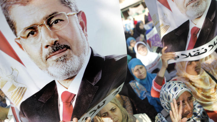 "Supporters of ousted Egyptian President Mohammed Morsi hold posters with Morsi's face and words in Arabic that read ""No to the coup,"" as they march in the Maadi district of Cairo on Monday, Aug. 19, 2013. Tensions in Egypt have soared since the army ousted Morsi, Hosni Mubarak's successor, in a July 3 coup following days of protests by millions of Egyptians demanding the Islamist president leave and accusing him of abusing his powers. But Morsi's supporters have fought back, staging demonstrations demanding that he be reinstated and denouncing the military coup. (AP Photo/Amr Nabil)"