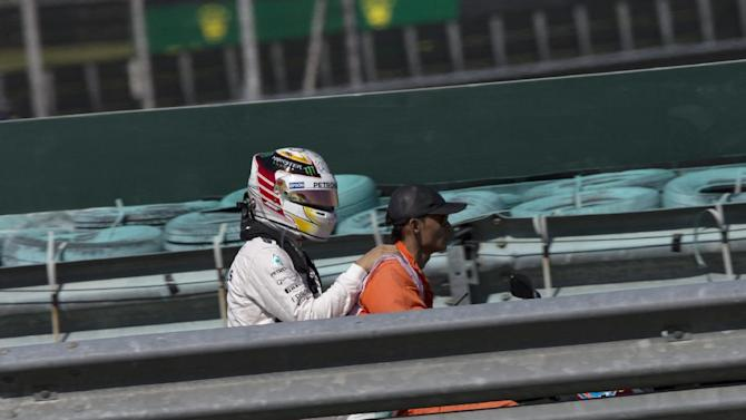 Mercedes driver Lewis Hamilton of Britain is driven back to his garage after stopping his car due to an engine failure during the first practice session for the Malaysian Formula One Grand Prix at Sepang International Circuit in Sepang, Malaysia, Friday, March 27, 2015. (AP Photo/Vincent Thian)