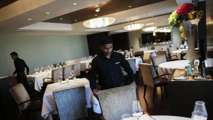 An employee of Le Cirque Signature restaurant prepares a table in Mumbai