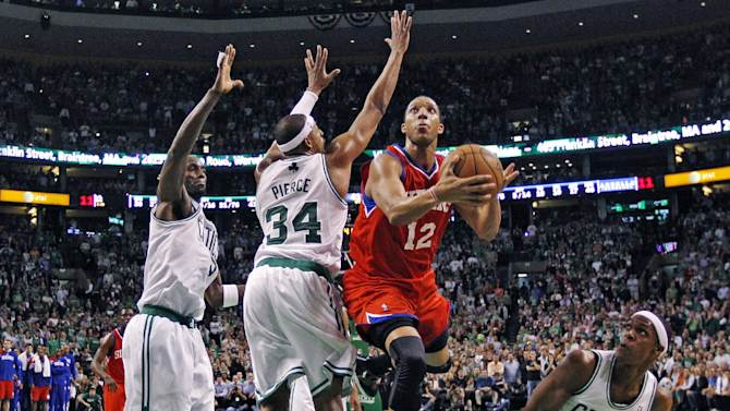 Philadelphia 76ers shooting guard Evan Turner (12) gets past Boston Celtics forward Kevin Garnett, left, small forward Paul Pierce (34), and guard Rajon Rondo to score the go-ahead basket in the final minute of the second half of Game 2 in their NBA basketball Eastern Conference semifinal playoff series in Boston, Monday, May 14, 2012. The 76ers won 82-81. (AP Photo/Charles Krupa)