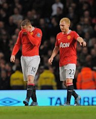 Manchester United players Paul Scholes (R) and Wayne Rooney react after conceding a goal against Manchester City during their English Premier League match at The Etihad Stadium in Manchester. City seized control of the Premier League title race after Vincent Kompany's first-half header powered them to a 1-0 win over bitter rivals United