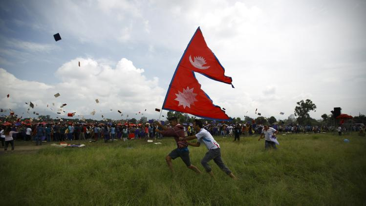 "Participants holding a Nepalese national flag run after completing an attempt to break the Guinness World Record for the ""Largest Human National Flag"" at Tundhikhel in Kathmandu"