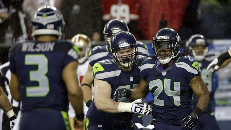 Seattle Seahawks' Marshawn Lynch (24) celebrates his touchdown against the San Francisco 49ers with Paul McQuistan, center, and quarterback Russell Wilson (3) in the first half of an NFL football game, Sunday, Dec. 23, 2012, in Seattle. (AP Photo/Elaine Thompson)