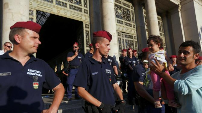 A man holds up a baby to police officers during demonstration by migrants outside entrance to main Eastern Railway station in Budapest