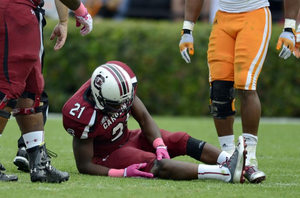 South Carolina running back Marcus Lattimore grabs his right knee after getting hit by Tennessee's Eric Gordon during the first half of an NCAA college football game Saturday, Oct. 27, 2012 at Williams-Brice Stadium in Columbia, S.C.  (AP Photo/Richard Shiro)