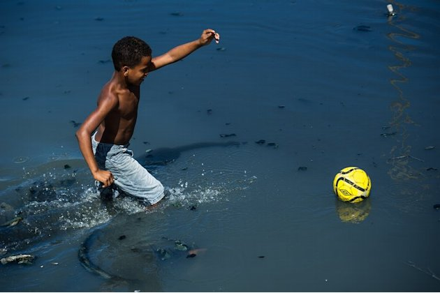 A boy wades through the polluted water of a canal to retrieve his football in the shantytown of Olinda,  June 18, 2013