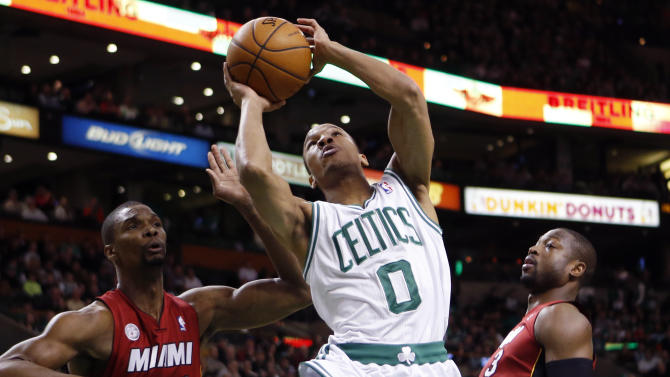 Boston Celtics' Avery Bradley (0) shoots between Miami Heat's Chris Bosh (1) and Dwyane Wade (3) in the first quarter of an NBA basketball game in Boston, Monday, March 18, 2013. (AP Photo/Michael Dwyer)