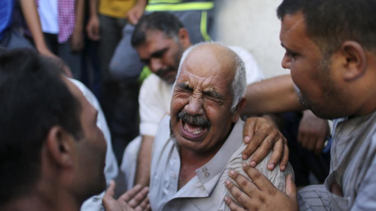 A grandfather of three Palestinian children cries outside a hospital morgue in Gaza City