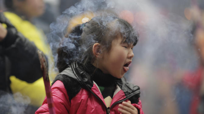 A child is choked by joss stick smoke while praying at a temple in Shanghai, China on Monday Feb. 11, 2013, on the second day of the Chinese Lunar New Year. Chinese celebrate the arrival of the Year of the Snake, according to the Chinese Zodiac. (AP Photo/Eugene Hoshiko)