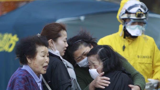 FILE - In this March 13, 2011 file photo, residents evacuated from areas surrounding the Fukushima nuclear facilities damaged by the March 11 massive earthquake and tsunami react during a check for radiation contamination in Koriyama city, Fukushima prefecture, Japan. Influential Japanese scientists who help set national radiation exposure limits have for years had trips paid for by the country's nuclear plant operators to attend overseas meetings of the world's top academic group on radiation safety. Some of these same scientists have consistently given optimistic assessments about the health risks of radiation, interviews with the scientists and government documents show. Their pivotal role in setting policy after the March 2011 tsunami and ensuing nuclear meltdowns meant the difference between schoolchildren playing outside or indoors and families staying or evacuating.  (AP Photo/Wally Santana, File)