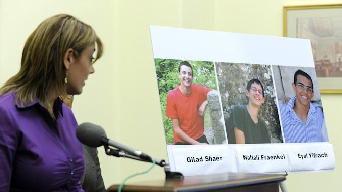 FILE - In this Tuesday, June 24, 2014 file photo, Leehy Shaer, the aunt of kidnapped Israeli-American teen Naftali Frenkel, looks over at a photo of the three missing teens during a news conference on Capitol Hill in Washington. Security officials said Monday, June 30, 2014 that the Israeli military has discovered the bodies of three Israeli teenagers who were kidnapped in the West Bank earlier this month. The search for the teens had become a national obsession, setting off a frantic manhunt and large crackdown on the Hamas militant group. (AP Photo/Susan Walsh, File)