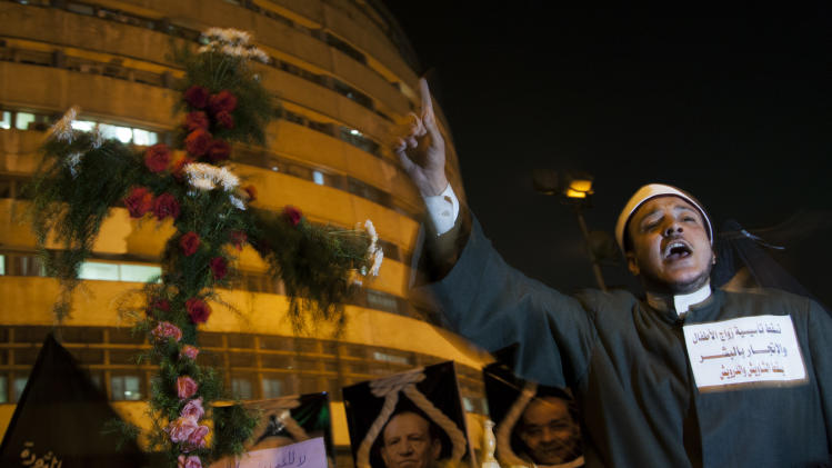 "An Egyptian Muslim cleric chants anti-Muslim Brotherhood slogans as he stands next to a cross made of flowers during a march marking the first anniversary of the victims who were killed during clashes with the military police in front of the National State T.V. building, known as Maspero, in Cairo, Egypt, Tuesday, Oct. 9, 2012. Muslim clerics, Christian priests, activists and former liberal lawmakers were among those marching to mark the anniversary of the ""Maspero massacre,"" referring to the name of the state TV building, where the clashes broke out. (AP Photo/Khalil Hamra)"