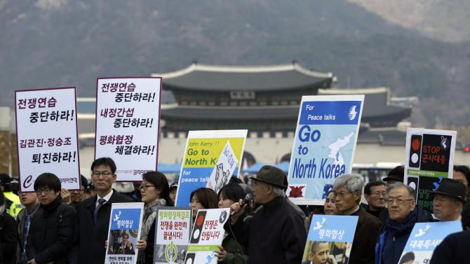 """South Korean protesters hold placards during a rally denouncing the joint military exercises between South Korea and U.S. and demanding U.S. Secretary of State John Kerry go to North Korea for peace talks, near the U.S. Embassy in Seoul, South Korea, Friday, April 12, 2013. Kerry is traveling to Asia to meet with U.S. allies and visit here on the first leg of his three-nation Asian tour. The letters read """"Stop war exercises."""" (AP Photo/Lee Jin-man)"""