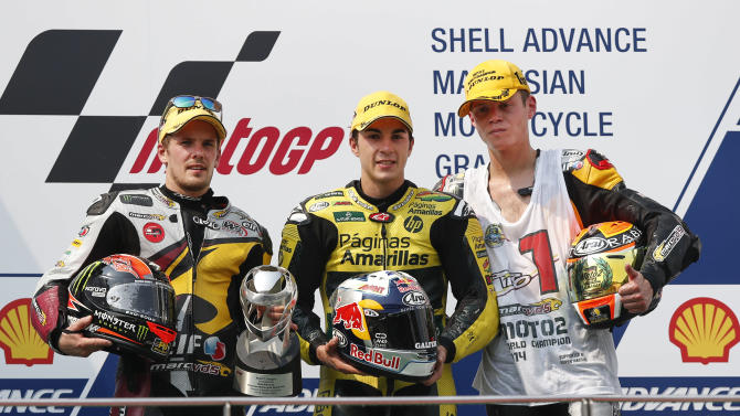 Moto2 rider Maverick Vinales of Spain, center, Mika Kallio from Finland, left, and Esteve Rabat of Spain pose during the awards ceremony during the Malaysian Motorcycle Grand Prix in Sepang, Malaysia, Sunday, Oct. 26, 2014. Vinales won the race, followed by Kallio and Rabat. (AP Photo/Vincent Thian)