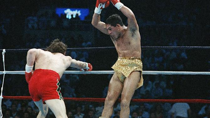 """FILE - In this March 7, 1989 file photo, Hector """"Macho"""" Camacho jumps out of the way of a punch thrown by Ray Mancini during the third round of their WBO Junior Welterweight Championship boxing match in Reno, Nev. Camacho, a boxer known for skill and flamboyance in the ring, as well as for a messy personal life and run-ins with the police, has died, Saturday, Nov. 24, 2012, after being taken off life support. He was 50.  (AP Photo/Eric Risberg, File)"""