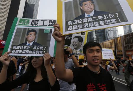Pro-democracy protesters carrying portraits of Hong Kong Chief Executive Leung march to his residence in Hong Kong