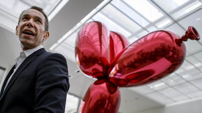 US artist Jeff Koons poses next to his sculpture 39Balloon Dog39 during an exhibition preview at the Fondation Beyeler museum in Basel Switzerland on May 11 2012