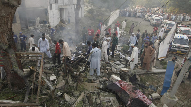 Pakistani volunteers and investigators gather at the site of an explosion in Karachi, Pakistan on Thursday, Nov. 8, 2012. A suicide bomber smashed a truck packed with explosives into housing for a paramilitary force protecting Pakistan's largest city, killing at least one person in the explosion Thursday morning that sent a large plume of smoke into the sky, officials said. (AP Photo/Fareed Khan)