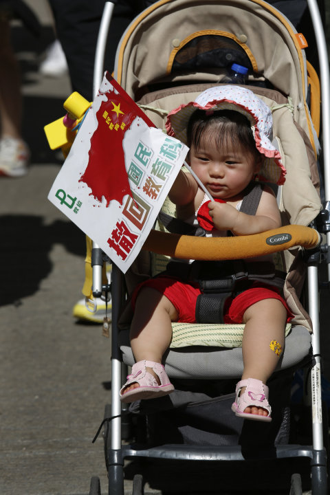 "A child holds a distorted Chinese national flag with a slogan ""Withdraw chinese patriotism classes"" on a stroller pushed by a parent during a march on a downtown street in Hong Kong  Sunday, July 29,"