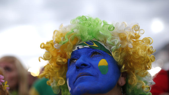 A fan of the Brazil national soccer team watches a live broadcast of the World Cup third-place soccer match between Brazil and Netherlands, inside the FIFA Fan Fest area on Copacabana beach, in Rio de Janeiro, Brazil, Saturday, July 12, 2014. (AP Photo/Silvia Izquierdo)