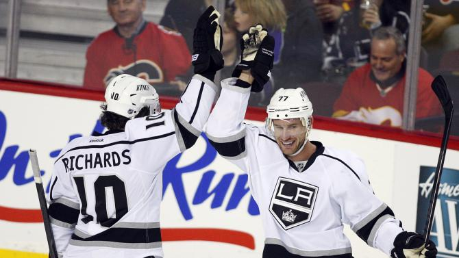 Los Angeles Kings' Jeff Carter, right, high fives teammate Mike Richards after scoring during third period of an NHL hockey action against the Calgary Flames in Calgary, Alberta, Wednesday, Feb. 20, 2013. The Los Angeles Kings beat the Calgary Flames 3-1. (AP Photo/THE CANADIAN PRESS/Jeff McIntosh)