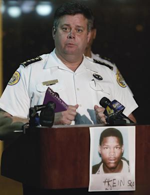 New Orleans Police Superintendent Ronal Serpas announces the issuance of an arrest warrant for 19-year-old Akien Scott in the Mother's Day shootings during a news conference in front of police headquarters in New Orleans, Monday, May 13, 2013. Scott's photo is on the front of the podium. (AP Photo/Bill Haber)