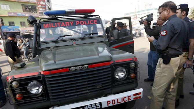Policemen stand beside an Army jeep after it was attacked by gunmen along a road in Karachi