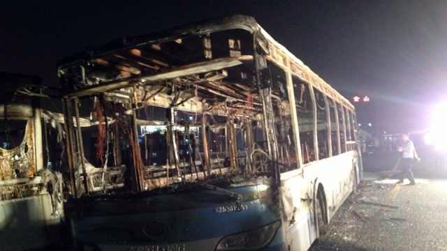 This image made with a mobile phone camera released by China's Xinhua News Agency shows the remains of an express bus that burst into flames in Xiamen, southeast China's Fujian Province on Friday, June 7, 2013. The express bus burst into flames on an elevated road in southeastern China on Friday, killing at least 30 people and injuring more than 30, state media reported. (AP Photo/Xinhua) NO SALES