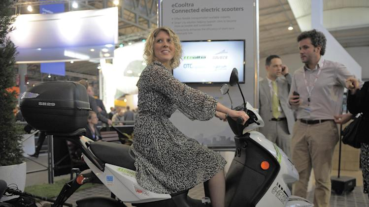 In this Tuesday, Feb. 26, 2013, photo, a woman sits on an eCooltra Connected electric scooters at the Mobile World Congress, the world's largest mobile phone trade show, in Barcelona, Spain. The first wave of the wireless revolution was getting people to talk to each other through cellphones. The second, it seems, will be getting things to talk to each other, with no human intervention: cars that talk to your insurance company's computers, bathroom scales that talk to your phone, and electric meters that talk to your air conditioners. So-called machine-to-machine technology all the buzz at this year's largest wireless trade show, and some analysts believe these types of connection will outgrow the traditional phone business in less than a decade. (AP Photo/Manu Fernandez)