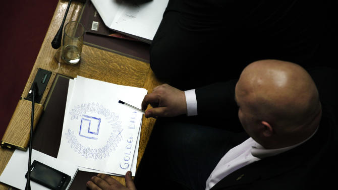 Lawmaker Ilias Panagiotaros, of the extreme right Golden Dawn party, sketches his party logo on a piece of paper during a debate in Parliament session in Athens early Friday Jan. 18, 2013. The party sought an investigation of two former prime ministers over an emerging scandal involving the handling by authorities of data on Greeks with Swiss bank accounts. Lawmakers rejected the proposal but voted by an overwhelming majority to investigate former finance minister George Papaconstantinou _ a probe backed by all political parties in the 300-member assembly. (AP Photo/Petros Giannakouris)