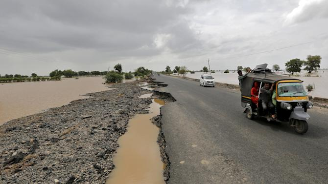 Vehicles move through the damaged national highway after heavy rains on the outskirts of Ahmedabad
