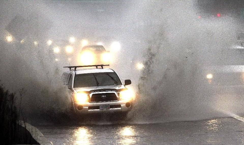 Traffic plows through high water as it merges onto Interstate 5 in Portland, Ore., Monday, Nov. 19, 2012. A powerful storm is pounding the Oregon coast, shutting down marine traffic in and out of several coastal rivers and closing part of highway U.S. 101. (AP Photo/Don Ryan)